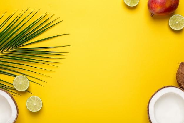 Backround amarelo com coco tropical, palmeira e frutas Foto Premium