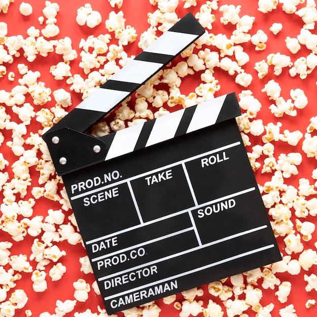 Badalo de filme sobre fundo vermelho com pipoca ao redor Foto gratuita