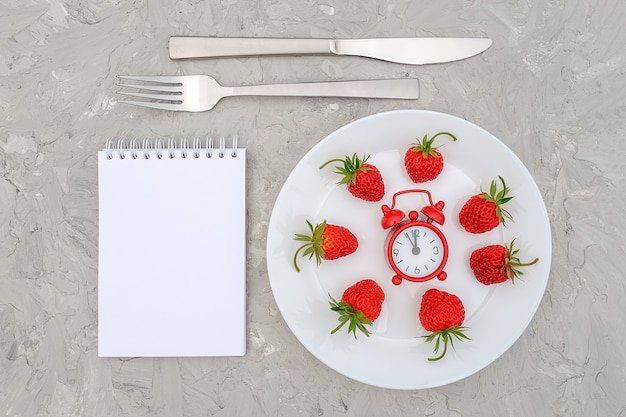 Baga de morangos maduros vermelhos na chapa branca, talheres, despertador vermelho e bloco de notas em branco na pedra cinza Foto Premium