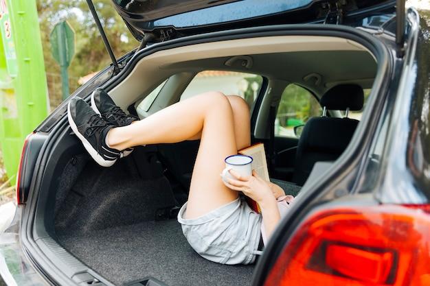 Bagageira aberta da máquina com pés femininos Foto gratuita