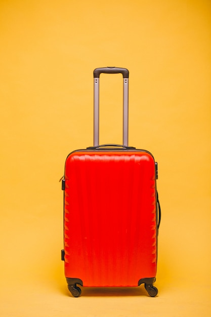 Bagagem vermelha sobre um fundo amarelo isolado Foto gratuita