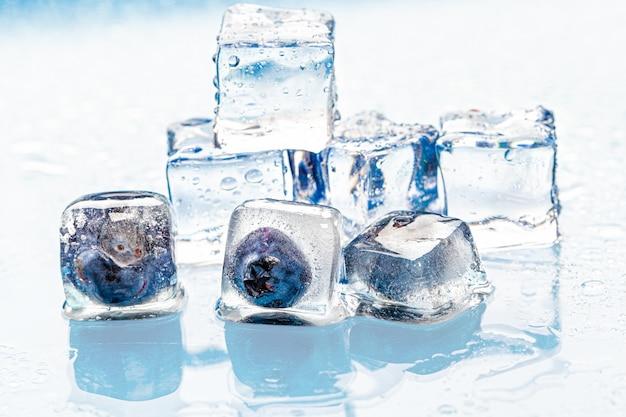 Bagas congeladas em cubos de gelo na rosa Foto Premium
