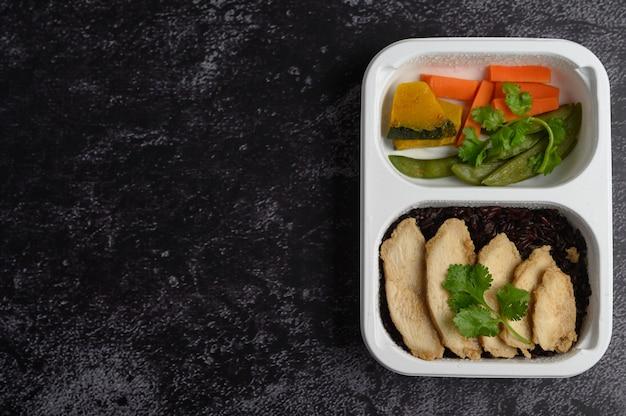 Bagas de arroz roxo cozidas com peito de frango grelhado folhas de abóbora, cenoura e hortelã em uma caixa plástica Foto gratuita
