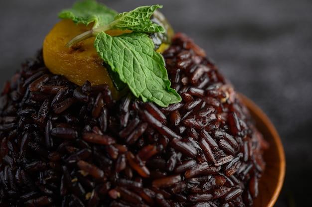 Bagas de arroz roxo cozido em um prato de madeira com folhas de hortelã e abóbora. Foto gratuita