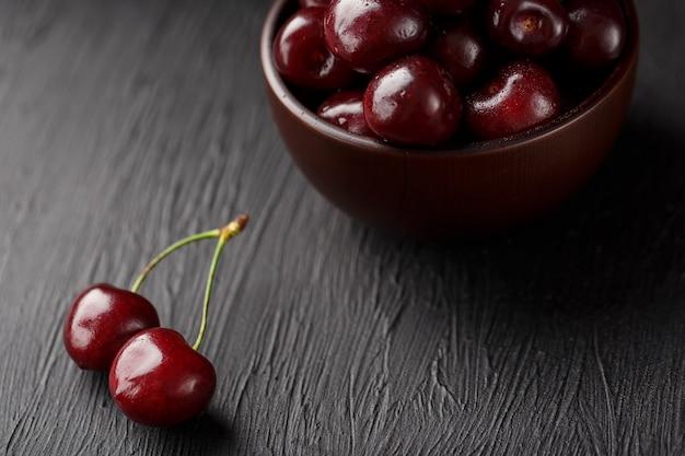 Bagas de cereja maduras e suculentas em preto Foto Premium