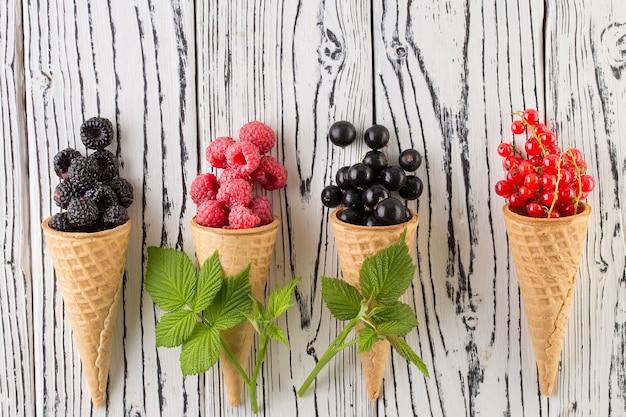 Bagas de verão no cone waffle em fundo branco de madeira Foto Premium