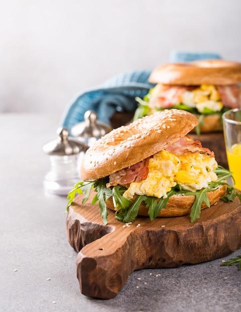 Bagels com ovos mexidos, rúcula e bacon frito Foto Premium