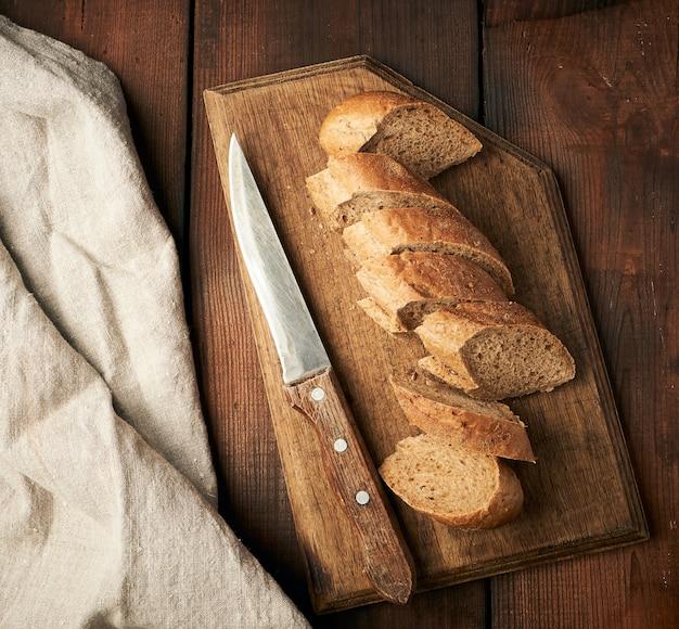 Baguete de farinha de centeio em fatias sobre uma tábua de madeira Foto Premium