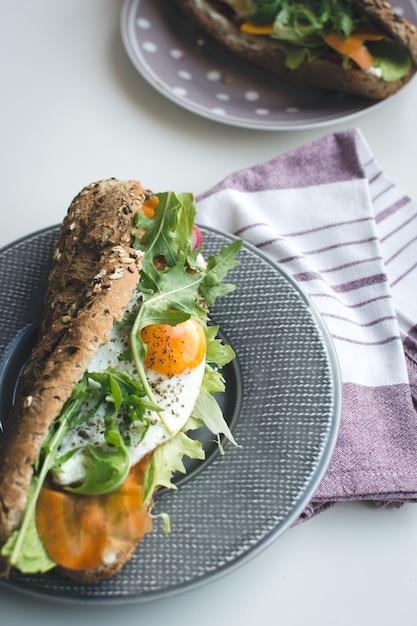 Baguete de trigo integral com ovo frito e rúcula Foto gratuita