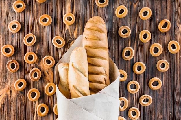 Baguetes embrulhados em papel rodeado de bagels no fundo de madeira Foto gratuita