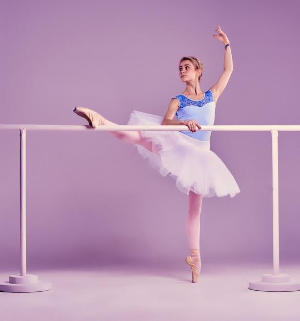 Bailarina clássica posando no bar de balé Foto gratuita