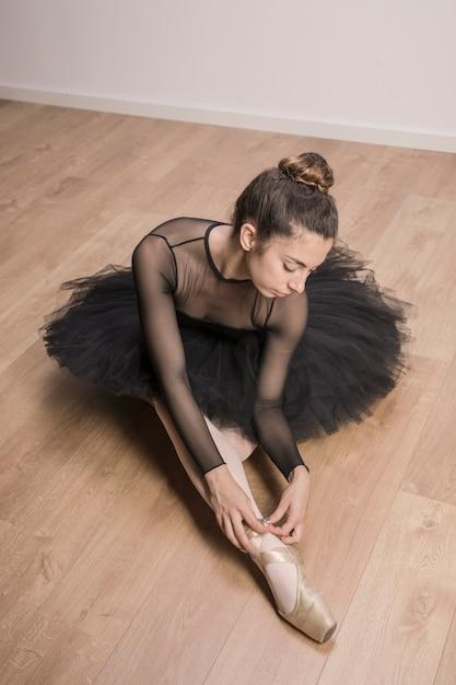 Bailarina de alto ângulo, amarrando o sapato de ponta Foto gratuita