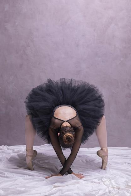 Bailarina de vista frontal, curvando-se em sapatos de ballet Foto gratuita