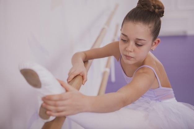 Bailarina encantadora jovem exercitar na escola de dança Foto Premium