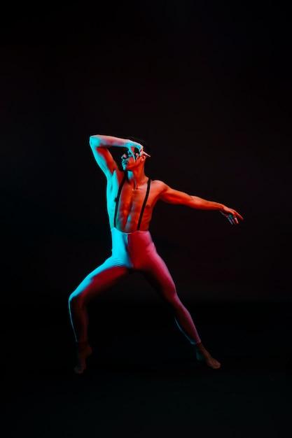 Bailarina masculina em malha com suspensórios em holofotes Foto gratuita