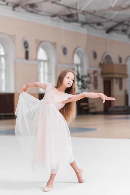 Bailarina no vestido rosa dançando na pista de dança Foto gratuita