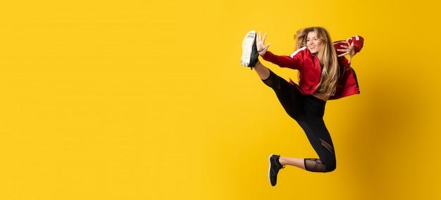 Bailarina urbana dançando sobre fundo amarelo isolado e pulando Foto Premium