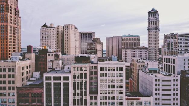Bairro com edifícios modernos coloridos e arranha-céus sob um céu nublado Foto gratuita