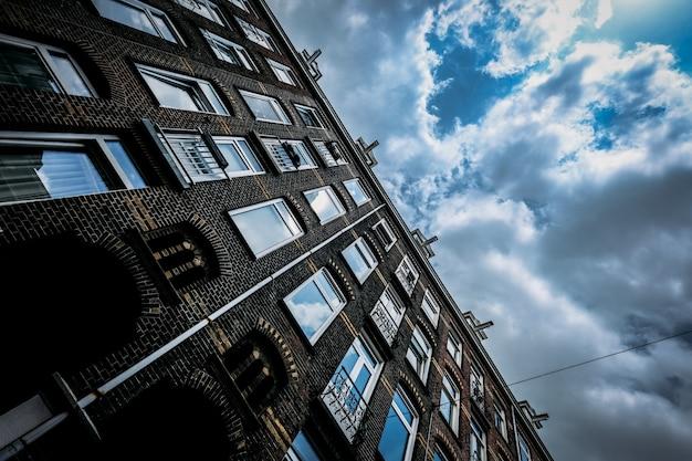 Baixo, ângulo, tiro, tijolo, predios, janelas, céu nublado Foto gratuita