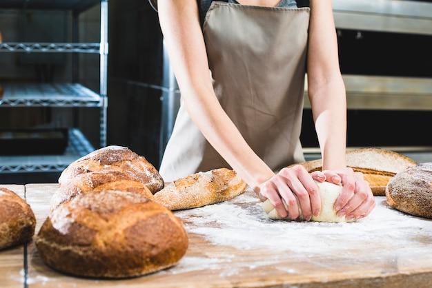 Baker feminino amassar a massa na mesa de madeira Foto gratuita