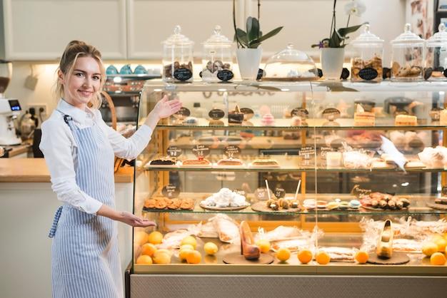 Baker feminino apresentando as várias pastelarias no armário de exposição transparente Foto gratuita