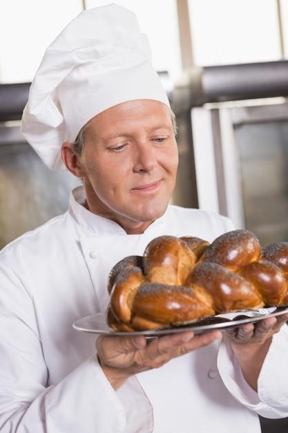 Baker que mostra o pão recém-assado Foto Premium