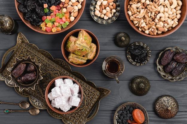 Baklava caseiro de delícia turca; datas; frutas secas e nozes na tigela metálica e barro sobre a mesa Foto gratuita