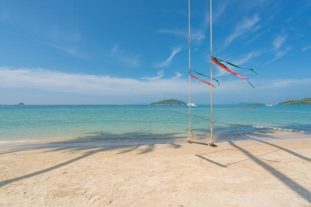 Balance o cair da palmeira do coco sobre a praia do verão com o mar da água clara e acene com o barco da velocidade em phuket, tailândia. conceito de verão, viagens, férias e férias. Foto Premium