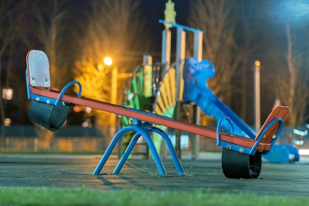 Balanço de gangorra no pátio da pré-escola com piso de borracha macia à noite. Foto Premium