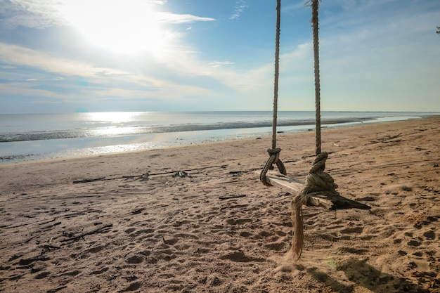 Balanço de madeira pendurado na praia. Foto Premium