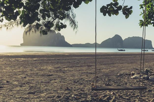 Balanço vazio no tom de cor vintage praia com pôr do sol Foto Premium
