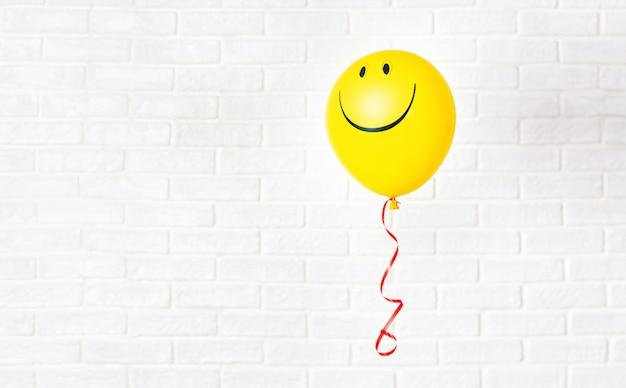 Balão amarelo com sorriso trava aganst parede branca Foto Premium