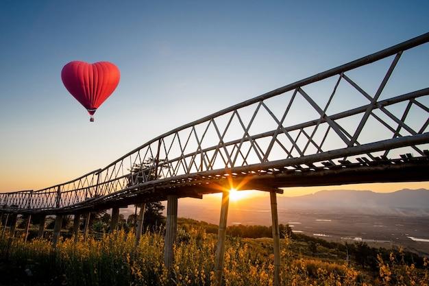 Balão de ar quente em forma de um coração sobre o pôr do sol na proibição doi sa-ngo chiangsaen, província de chiang rai, tailândia. Foto Premium