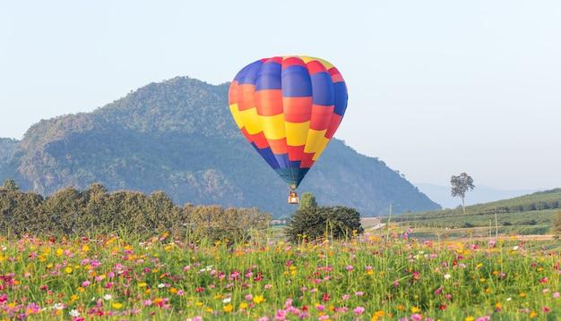 Balão de ar quente sobre campos de flores com fundo de montanha Foto Premium