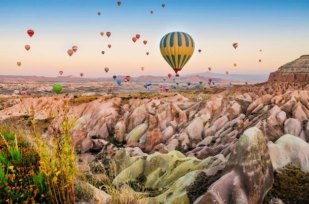 Balão de ar quente sobrevoando a paisagem rochosa na capadócia turquia Foto Premium