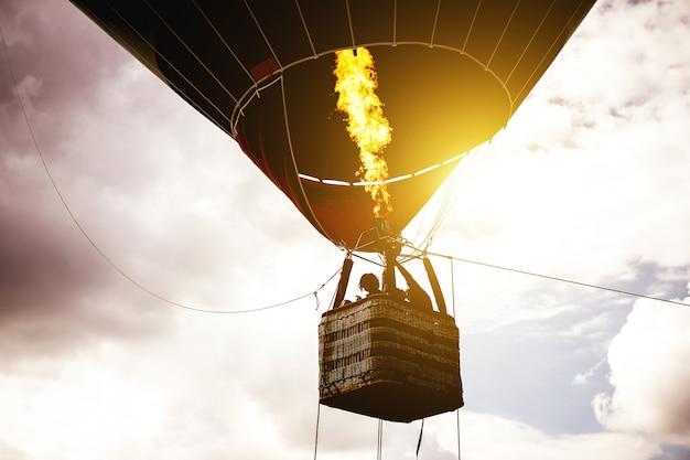 Balão de ar quente voando em um céu nublado ao nascer do sol Foto Premium