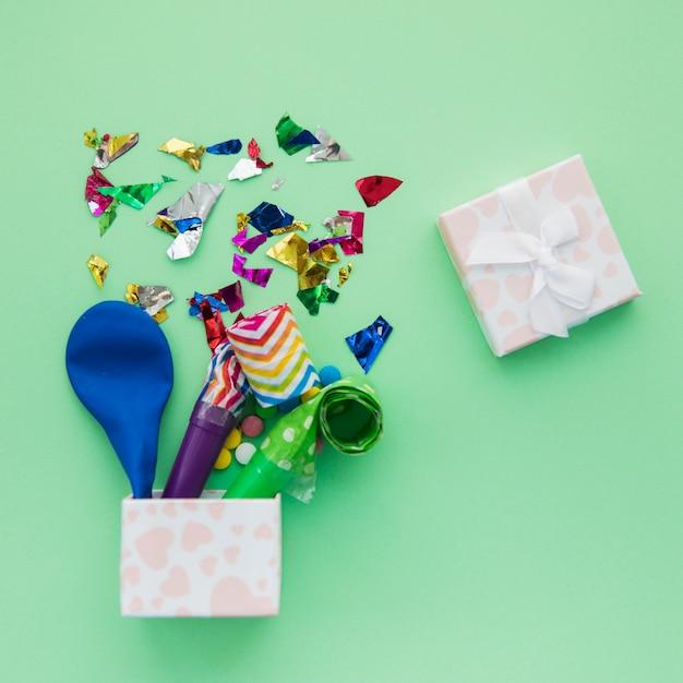 Balão esvaziado; sopradores de chifre de festa e confetes na caixa aberta sobre fundo verde Foto gratuita
