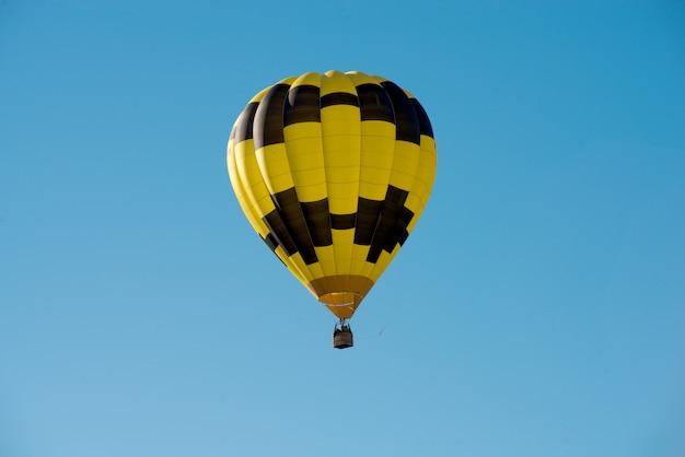 Balão preto e amarelo em um céu azul Foto Premium