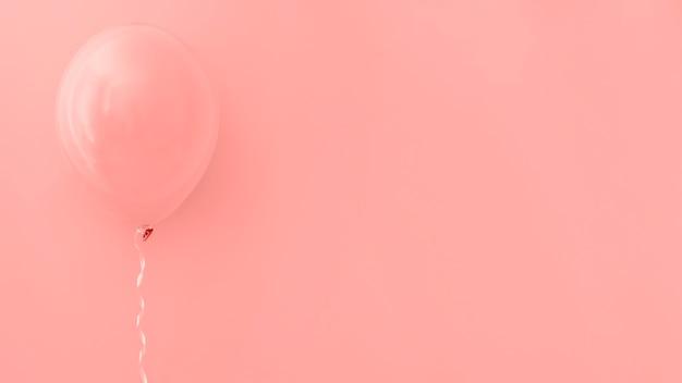 Balão rosa em fundo rosa Foto gratuita