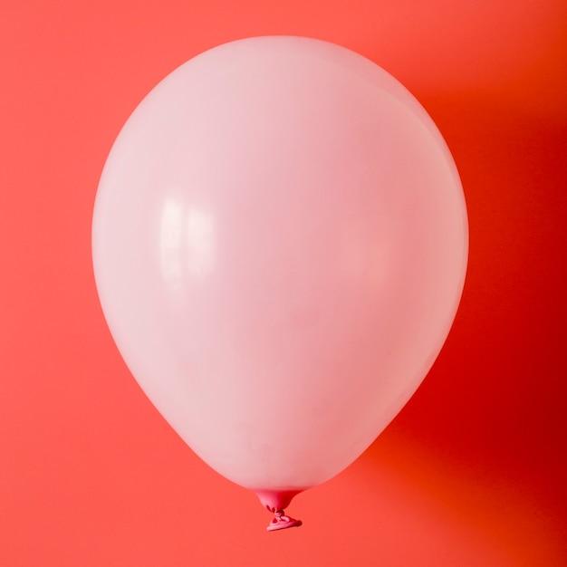 Balão rosa em fundo vermelho Foto gratuita
