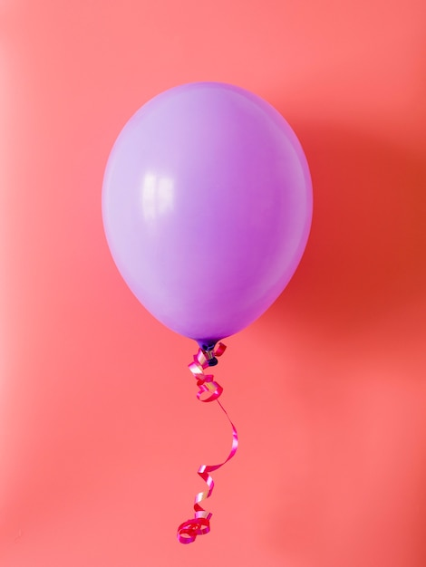 Balão roxo em fundo rosa Foto gratuita