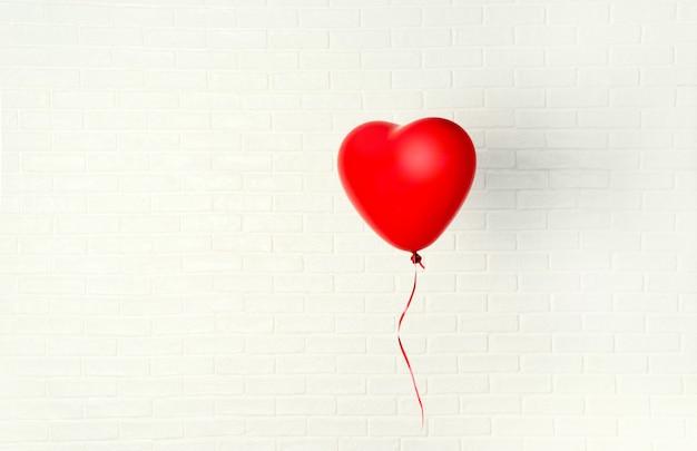 Balão vermelho com forma de coração trava aganst parede branca Foto Premium