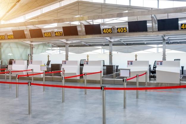 Balcões de check-in vazios para entrega de bagagem com caminhos cancelados com uma fita vermelha para diferenciar passageiros no terminal do aeroporto. Foto Premium