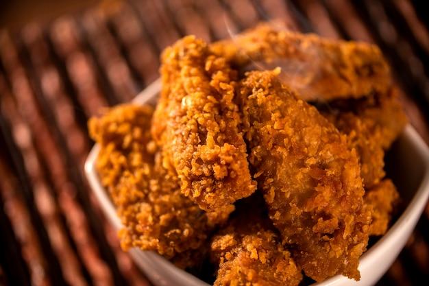 Balde cheio de frango frito kentucky crocante com fumaça no fundo marrom. foco seletivo. Foto Premium