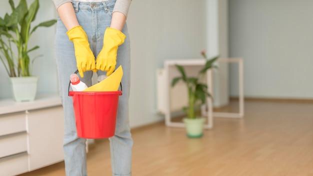 Balde com material de limpeza realizada por mulher com luvas Foto gratuita