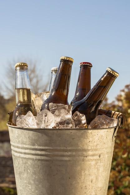 Balde de baixo ângulo com cubos de gelo frio e garrafas de cerveja Foto gratuita