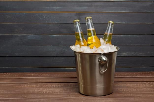 Balde de cerveja na mesa de madeira Foto Premium
