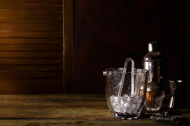 Balde de gelo de vidro com acessórios de bar em fundo escuro de madeira Foto Premium