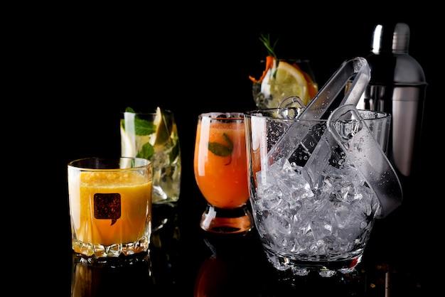 Balde de gelo de vidro e cocktails diferentes em vidro com acessórios bar isolado no preto Foto Premium