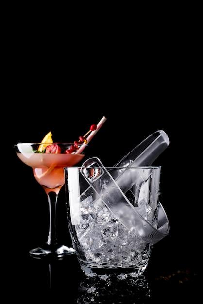 Balde de gelo de vidro e margarita cocktail em vidro isolado em preto Foto Premium